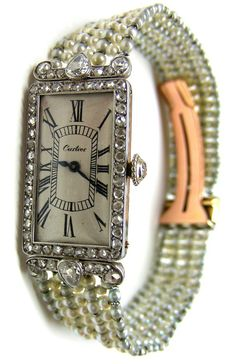 Early 20th century platinum, diamond and pearl dress-watch by Cartier, Paris, c.1905 The white enamel dial with black painted Roman numerals, to a pavй-set rose-cut diamond bezel and scrolling pear-cut diamond set shoulders, with diamond set winder, to a seven row white and grey pearl bracelet concealing a rose gold and platinum deployant clasp. S.J. Phillips Ltd.