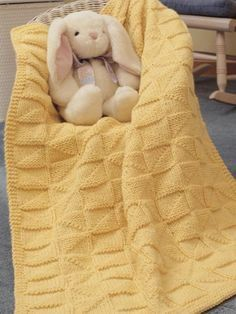 Knit up a reversible afghan that is full of texture and warmth. It's just the right size for cuddling your precious little one. Designed by Laura Polley