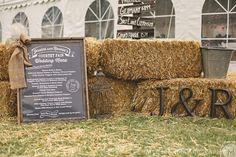Hay bale wedding decor outside the wedding tent. Large chalk board stlye menu.