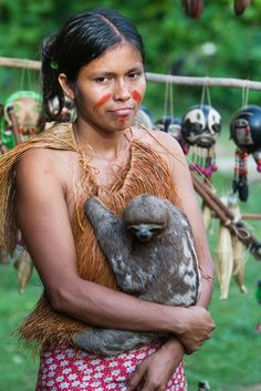 A girl of the Yagua tribe near Iquitos, Peru, holds her pet baby sloth.