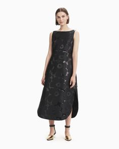 The sleeveless Jalokivi dress is made from a metallic jacquard in the Unikko pattern. The dress has a boatneck, a back concealed zipper closure at the neck, french darts and a horizontal seam at the waistline. The dress is fully lined and has a round hem