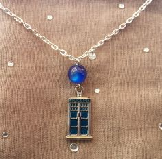 This necklace features a Police Box Charm beneath a lovely blue bead.    The necklace measures about 20 inches in length and is finished with a