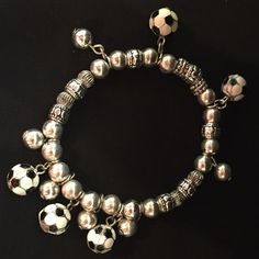 Soccer Theme Silver Tone Stretch Bracelet Whether playing or cheering, soccer season is right around the corner. 5 Enamel soccer ball charms adorn this silver tone stretch bracelet. Jewelry Bracelets