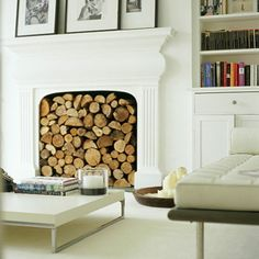 Love the stacked logs in the fireplace - what a calming white room too.  Built in cabinetry looks great