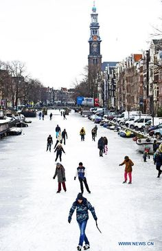 NETHERLANDS-AMSTERDAM-ICE CANALS. People skate on the frozen canal