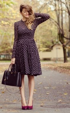Purple patterned dress, with knee-length pleated skirt, long sleeves and high neckline, paired with purple handbag and lighter coloured heels.