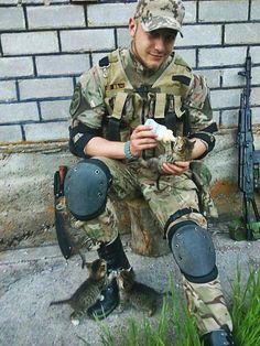 Ukrainian soldier feeding a cat