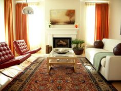 Touches of red, burnt orange and brown warm up this lovely living room. To help a space look pulled together, place at least the front legs of furniture on the rug, as seen here with the large Oriental one.
