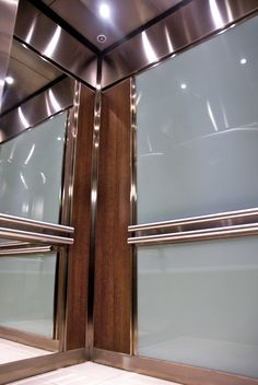 The rear wall of this Elevator Interior is fitted with back painted safety glass above and below the handrail coloured with an aqua blue to compliment the wood panels. Two mirrors on both sidewalls are divided above and below a raised stainless steel handrail support band and raised laminate wall panels on either side. All panels are framed with stainless steel 'J' style trims.  Wall to wall porcelain flooring with matching grout completes the interior providing a durable high traffic…