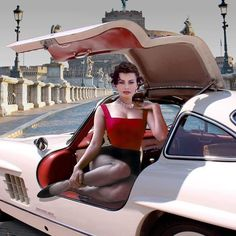Two beauties caught in One Frame - Sophia Loren sitting on the door sill of the Mercedes 300SL Gullwing, introduced in 1954 and fastest production car of its day.