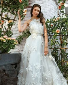 "Breeze down the aisle in a floaty chiffon dress embellished with windblown floral appliques. Kevan Hall White Label ""Virginia"" gown. Macklowe Gallery yellow-gold bracelet."