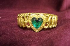 Pretty goldtone stretch Sweetheart bracelet from the 1950's made by Pittman and Keeler (marked inside) and marked American Queen, with green faceted heart-shaped stone. My measurements are for the heart only. Good vintage condition with some wear to the gold from use and age.  $45.00