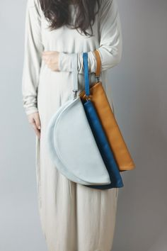 Circle leather clutch. Folded over, zipper closure.    Made of natural leather from Italy.  Unlined.    Available colors:  - cobalt blue,  - light
