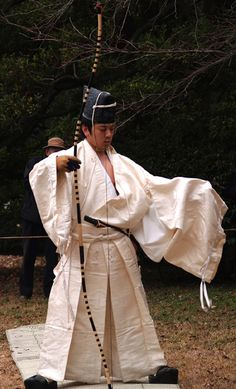 Shintoism - Momote-shiki is a Shinto archery ritual held to commemorate Seijin-no-hi or Coming of Age Day, in the precincts of Meiji Shrine in Shibuya, Tokyo. - A Shinto Priest loosens and removes his left sleeve so it will not hinder his shooting.