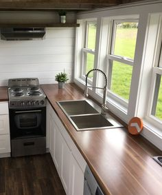 The kitchen is equipped with a stainless steel freestanding range, apartment size refrigerator, and a large butcher block counter.