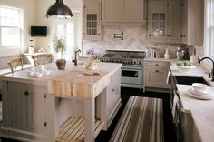 source: Bakes and Company      Gorgeous gray kitchen design with soft gray painted shaker kitchen cabinets, soft gray kitchen island with butcher block, oil-rubbed bronze pot filler, oil-rubbed bronze yoke pendant, French cafe X-back counter stools and green & blue striped kitchen runner.