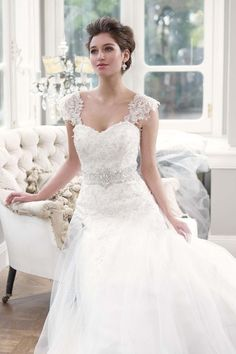 Mia Solano. Bridal Tulle ball gown wedding dress features sweetheart neckline. Beaded appliques on bodice and beaded waist detail. Lace shoulder straps are removable. Chapel length train. Ball gown wedding dress with lace-up closure available colors White, Silver, Ivory and Oyster.