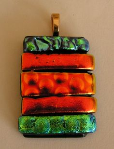 Strips of vibrant coloured Dichroic glass make up this unique pendant. Made in May 2015 . Unique Glass Art by Marion.