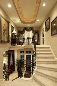 The staircase is detailed with custom designed wrought iron. Risers are stenciled. Stenciling is repeated on domed ceiling. Landing at mezzanine level.