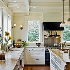 Cream white kitchen, no uppers, no upper cabinets, large stove with stainless steel Backsplash and black hood, marble countertops, ceiling beams