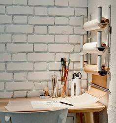 Três filas de dois porta-rolos GRUNDTAL, montados na parede na vertical a segurar rolos de papel para desenhar