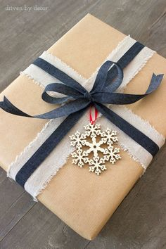 Holiday present wrapped beautifully but simply with linen ribbon and wood snowflake ornament