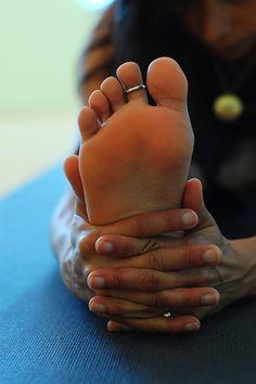 woman doing yoga, head to knee pose janu sirsasana w/ toe ring love that!