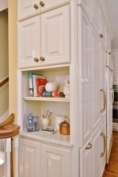 A small kitchen space between cabinets for cookbooks and small decor items.   Aston Design Studio ᘡղbᘠ