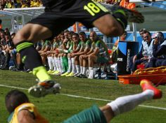 Australia's reserve players watch as Spain's Jordi Alba (top) and Australia's Matthew Leckie fight for the ball during their 2014 World Cup Group B soccer match at the Baixada arena in Curitiba June 23, 2014. REUTERS/Stefano Rellandini