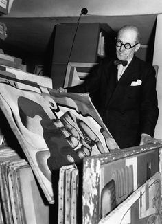 Le Corbusier in his flat looking at some of his paintings circa 1940 in Paris France