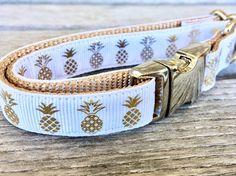 Gold Pineapple Dog Collar is a 5/8W white grosgrain ribbon with a gold foil Pineapple print sewn onto a 5/8 wide tan nylon webbing. Collar has all SILVER colored metal hardware, including a triglide, a side release buckle, and welded steel D ring. **Gold foil designs will eventually start to lose its shine, even with normal wear and tear. **  Interested in a matching leash? Treat yo self! Leash will come will come with same ribbon as listed here on 5/8 wide, 100% nylon webbing ...