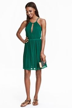 Short, pleated halterneck dress with narrow shoulder straps that cross at the back, a low-cut neck at the front and an elasticated seam at the waist. Jersey