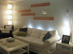 A large statement in the corner. uplights behind a sofa to illuminate a large wall.