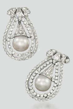 A PAIR OF ART DECO NATURAL PEARL AND DIAMOND CLIP BROOCHES. Each designed as a grey natural pearl with diamond-set cap suspended within a circular-cut diamond collet and rose-cut diamond double surround to the scrolling diamond-set surmount, circa 1920, 2.8cm long. #ArtDeco #ClipBrooch