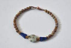 This Designs by s.e.K bracelet features a round sesame jasper stone, surrounded by brushed brass, triangular lapis lazuli and round jasper beads, closed with an antique copper-plated brass button clasp.