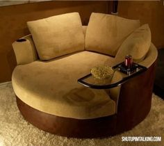 Tan circular sofa chair with cup holder and floating glass table