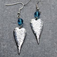 Long Heart Earrings  Lovely hammered texture pewter drop earrings featuring a blue glass bead on silver plated earwires . Handcrafted in the heart of Cornwall Supplied in a gift box.  Height 60mm (including hooks) Width 15mm