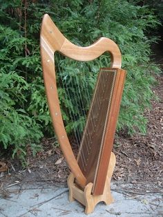 "Susan Reid-Adam and Charles Sabatino donated this beautiful handcrafted harp. The front pillar and neck are made of solid mahogany; the sound box is Philippine mahogany and American walnut veneers on white poplar frame, with patterned wood and genuine abalone inlays. Includes a solid oak display stand, tuning key, and ""Teach Yourself to Play the Folk Harp"" instructional by Sylvia Woods. This harp is dated inside the sound box and named ""Susan."" All proceeds will go to the school!"