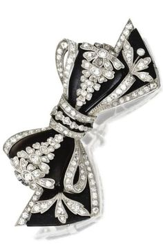 Platinum, Diamond and Onyx Bow Brooch, Circa 1915. The stylised bow brooch composed of onyx sections, edged and overlaid with platinum, set with old European-cut and single-cut diamonds. #BelleEpoque #antique #brooch