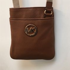 Michael Kors cross body bag. Brown Brown Michael Kors cross body handbag purse in tan/brown leather. Gently used. Please make me an offer. 7.5 inches along the bottom and 8.5 from top to bottom. Michael Kors Bags Crossbody Bags