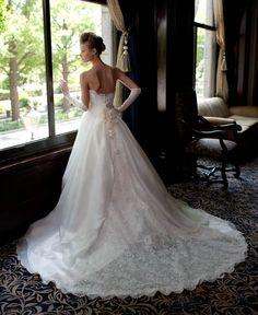 """軽やかなシルクオーガンジーのスカートは花嫁が動くたびに、風をはらむエアリーで優しいシルエットを演出する。サッシュベルトがより一層ウエストを細く見せてくれる、プリンセスラインのビスチェドレス。<span id=""""more-214""""></span>ふんわりと舞うスカートが、とてもピュアな印象を与えるバックスタイル。"""