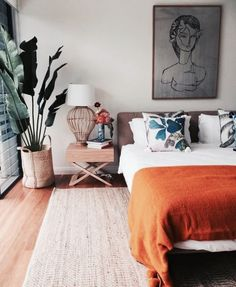 Light neutral bedroom decor ideas. I love the contrast of the blue pillows with the orange blanket. Such a cozy bedroom!
