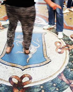 """Buongiorno!  Curiosità su Milano. Galleria Vittorio Emanuele II - Milano  Nellottagono centrale oggi luogo privilegiato per eventi e installazioni è situato sul pavimento il simbolo araldico dei Savoia con una croce bianca in campo rosso ed il famoso toro raffigurato con gli """"attributi"""" in vista.  L'usanza dice che porti fortuna porre il piede sopra gli attributi del toro (simbolo di forza e vigore) e compiere una rotazione ad occhi chiusi facendo perno su quel piede. Migliaia di turisti e…"""