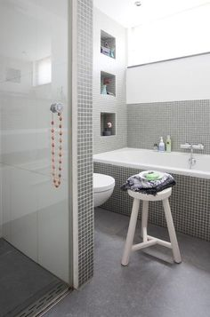Attractive modern grey bathroom ideas with rectangle standart tub also white toilet as well wooden bath seating in small room designs home inspiration Grey Bathroom Wall Tiles, Mosaic Bathroom, Bathroom Tile Designs, Grey Bathrooms, Bathroom Colors, White Bathroom, Bathroom Interior, Modern Bathroom, Small Bathroom