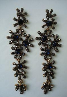 Lindo e sofisticado par de brincos pendentes, em metal no tom bronze adornado com cristais azul marinho e grafite.