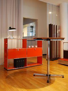 USM Haller sideboard in pure orange and USM Kitos Table circular. Exhibition at Partner Unternehmensgestaltung, Stuttgart, Germany. www.usm.com