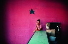Photography by Alex Webb.  fuschia, pink, star, turquoise, green, color, woman, bar, waiting