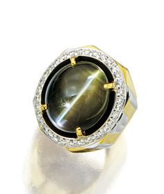 CAT'S-EYE CHRYSOBERYL AND DIAMOND RING.  Centring on an oval cabochon cat's-eye chrysoberyl weighing 32.40 carats, encircled by brilliant-cut diamonds, amid a broad shank, mounted in 18 karat white and yellow gold.