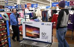 A Walmart employee helps a customer with a 50' TV on sale for $218 on Black Friday in Broomfield, Colorado November 28, 2014.  REUTERS-Rick Wilking