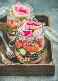 #Close-up of healthy vegetarian salad  Close-up of healthy take-away jars. Vegetable and chickpea sprout vegan salad in glass jars in wooden tray grey concrete background selective focus. Clean eating detox raw food dieting concept